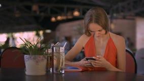Flickan surfar internet som använder Smartphone, sitter på tabellen lager videofilmer