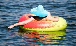 Flickan svävar på en behållare på sjön Royaltyfri Bild