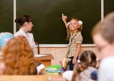 Flickan svarar frågor av lärare nära en skolförvaltning Royaltyfri Foto