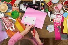 Flickan syr dockakläder, den bästa sikten som syr tillbehör bästa sikt, sömmerskaarbetsplatsen, många anmärker för handarbete, ha Royaltyfria Foton
