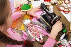 Flickan syr dockakläder, den bästa sikten som syr tillbehör bästa sikt, sömmerskaarbetsplatsen, många anmärker för handarbete, ha Royaltyfria Bilder