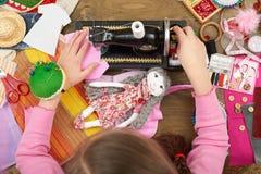Flickan syr dockakläder, den bästa sikten som syr tillbehör bästa sikt, sömmerskaarbetsplatsen, många anmärker för handarbete, ha Arkivfoto