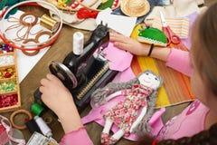 Flickan syr dockakläder, den bästa sikten som syr tillbehör bästa sikt, sömmerskaarbetsplatsen, många anmärker för handarbete, ha Fotografering för Bildbyråer