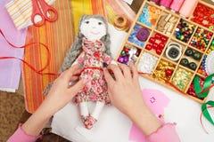 Flickan syr dockakläder, den bästa sikten som syr tillbehör bästa sikt, sömmerskaarbetsplatsen, många anmärker för handarbete, ha Royaltyfri Foto