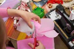 Flickan syr dockakläder, den bästa sikten som syr tillbehör bästa sikt, sömmerskaarbetsplatsen, många anmärker för handarbete, ha Arkivfoton