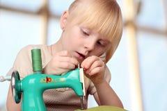 Flickan syr på barns symaskin Arkivbilder