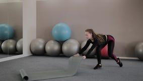 Flickan täcker kondition som är matt i idrottshallen arkivfilmer