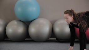 Flickan täcker kondition som är matt i idrottshallen lager videofilmer