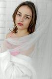Flickan täcker sig den genomskinliga gardinen Arkivfoto