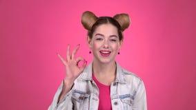 Flickan tänker och visar ok Rosa bakgrund stock video