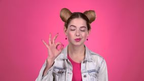 Flickan tänker och visar ok Rosa bakgrund långsam rörelse stock video