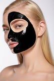 Flickan tar av den svarta kosmetiska maskeringen från hennes framsida arkivfoto