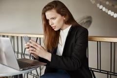 Flickan tar bilden av bärbar datorskärmen Inomhus skott av trendigt europeiskt flickasammanträde i kafé över anteckningsboken som arkivbild