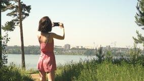 Flickan tar bilder av staden och havet lager videofilmer