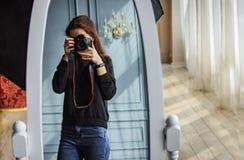 Flickan tar bilder i spegeln på en yrkesmässig kamera arkivfoto