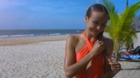 Flickan tar duschen på stranden mot den bildmässiga havcloseupen lager videofilmer