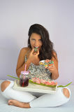Flickan tar en tugga av amerikanska donuts Royaltyfri Fotografi
