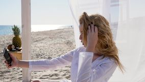 Flickan tar foto på mobiltelefonen, strand i sommar, selfie på minnet, semestern på tropiska öar, sexig flicka lager videofilmer