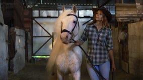 Flickan tar hästen ut ur stallen Stående Selektiv fokus lager videofilmer
