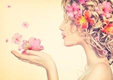 Flickan tar härliga blommor i hennes händer Arkivbilder