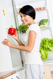 Flickan tar röd peppar från den öppnade kylen arkivfoto