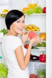 Flickan tar vattenmelon från den öppnade kylen arkivfoton