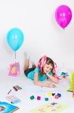 Flickan tecknar att ligga på ett golv royaltyfria bilder