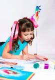 Flickan tecknar att ligga på ett golv arkivbild
