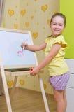 Flickan tecknar en markör på det vita brädet royaltyfri fotografi