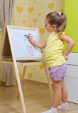 Flickan tecknar en markör på det vita brädet royaltyfri foto