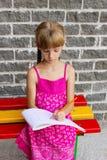 Flickan tecknar sittande bänk 5055 för album royaltyfri fotografi