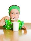 Flickan äter med en skedmejeriprodukt. Arkivfoto