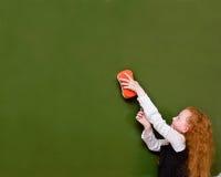 Flickan torkar den svart tavlan, med en svamp Arkivbilder
