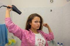 Flickan torkar hennes hår fotografering för bildbyråer