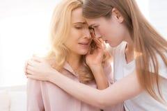 Flickan tröstar en vuxen kvinna som gråter arkivbilder
