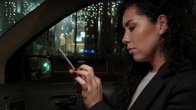 Flickan trycker på pekskärmen av en mobiltelefon, medan sitta i bilen och leendena stock video