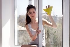 Flickan tvättar ett fönster Arkivbilder