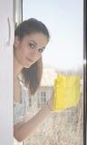 Flickan tvättar ett fönster Arkivfoto