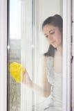 Flickan tvättar ett fönster Arkivbild