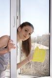 Flickan tvättar ett fönster Arkivfoton