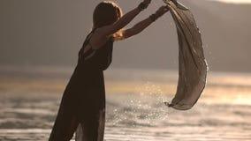 Flickan tvättar genomskinlig svart pareo för kläder i floden lager videofilmer
