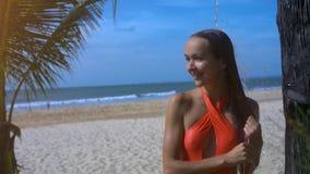 Flickan tvättar långt hår under dusch på stranden vid havet stock video