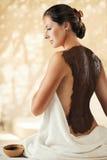 Flickan tycker om chokladkroppmaskeringen i en brunnsortsalong royaltyfria foton