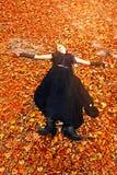 Flickan tycker om de sista solstrålarna i orange höst arkivfoton