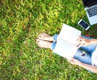 Flickan tycker om läseboken och spelar bärbara datorn på gräset som sparas av, parkerar arkivbild