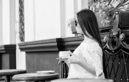 Flickan tycker om morgonkaffe V?ntande p? datum Kvinnan i solglas?gon dricker kaffe utomhus E royaltyfria foton