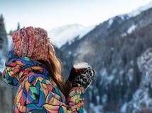 Flickan tycker om snönedgångarna Den unga kvinnan i en stucken form dricker te i skogen under ett snöfall tonat foto royaltyfri fotografi