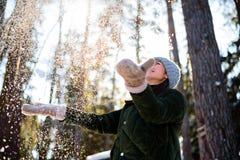 Flickan tycker om vintern, den frostiga dagen, snö spela med snö, kastar en kvinna vit lös snö in i luften Gå med vinterskogen arkivfoton
