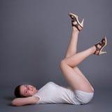 Flickan underligger på en grå bakgrund Arkivfoto