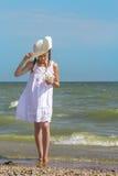Flickan undersöker korallen på stranden Arkivbilder